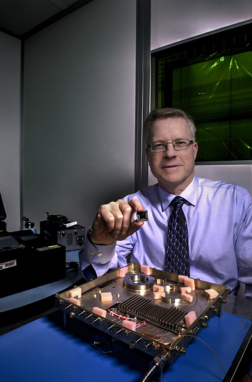 CAPTION NASA laser expert Mike Krainak and his team plan to replace portions of this fiber-optic receiver with an integrated-photonic circuit, whose size will be similar to the chip he is holding. The team then plans to test the advanced modem on the International Space Station. CREDIT Credits: NASA/W. Hrybyk