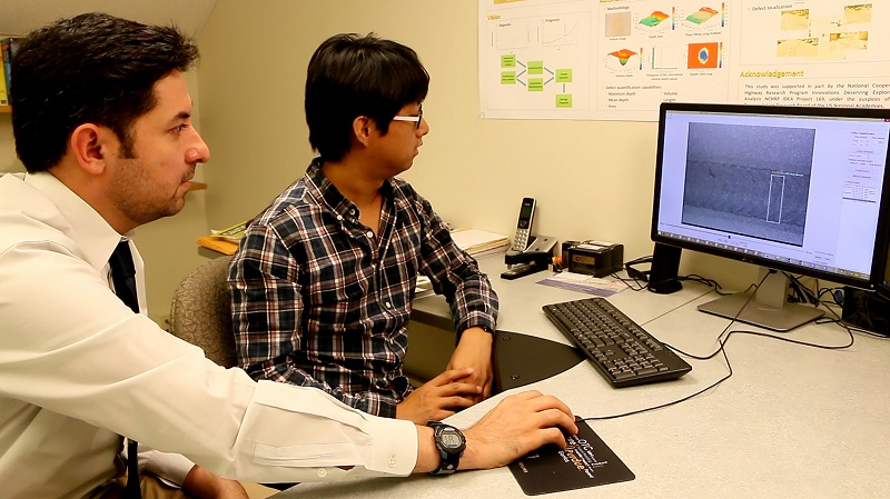 Mohammad R. Jahanshahi, left, an assistant professor in Purdue's Lyles School of Civil Engineering, and doctoral student Fu-Chen Chen review results using the new system. (Purdue University image/Erin Easterling)